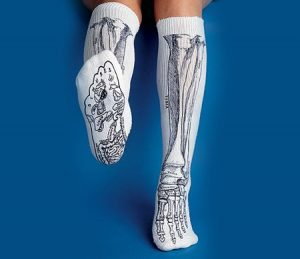 Two matching white socks with a black and gray skeleton design worn below the knee. Person wearing them has right foot extended showing skeleton foot design below.