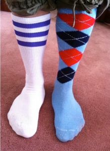 Two mismatched socks worn below the knee on a person. The right is a white sock with three blue bands along the top. The left sock is blue with a red, navy, and white argyle design on the leg portion.