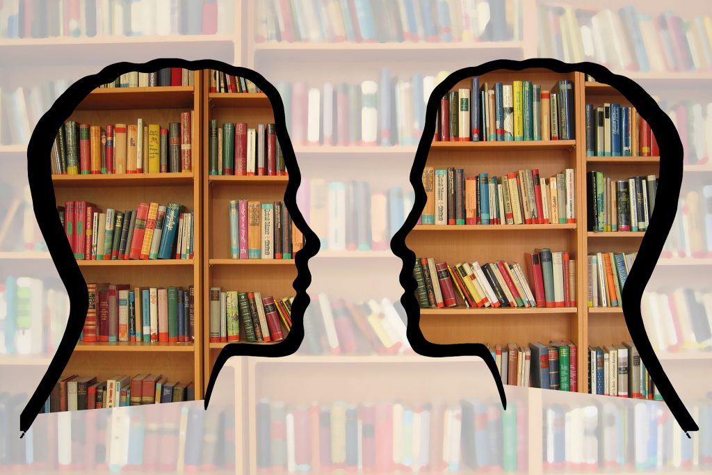 Two clear silhouettes facing each other in front of bookshelves with muted colours around the silhouettes.