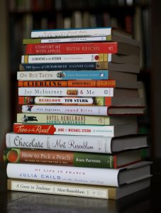 Image of a stack of fiction and non-fiction books ordered from largest to smallest book size of varying colours and format.