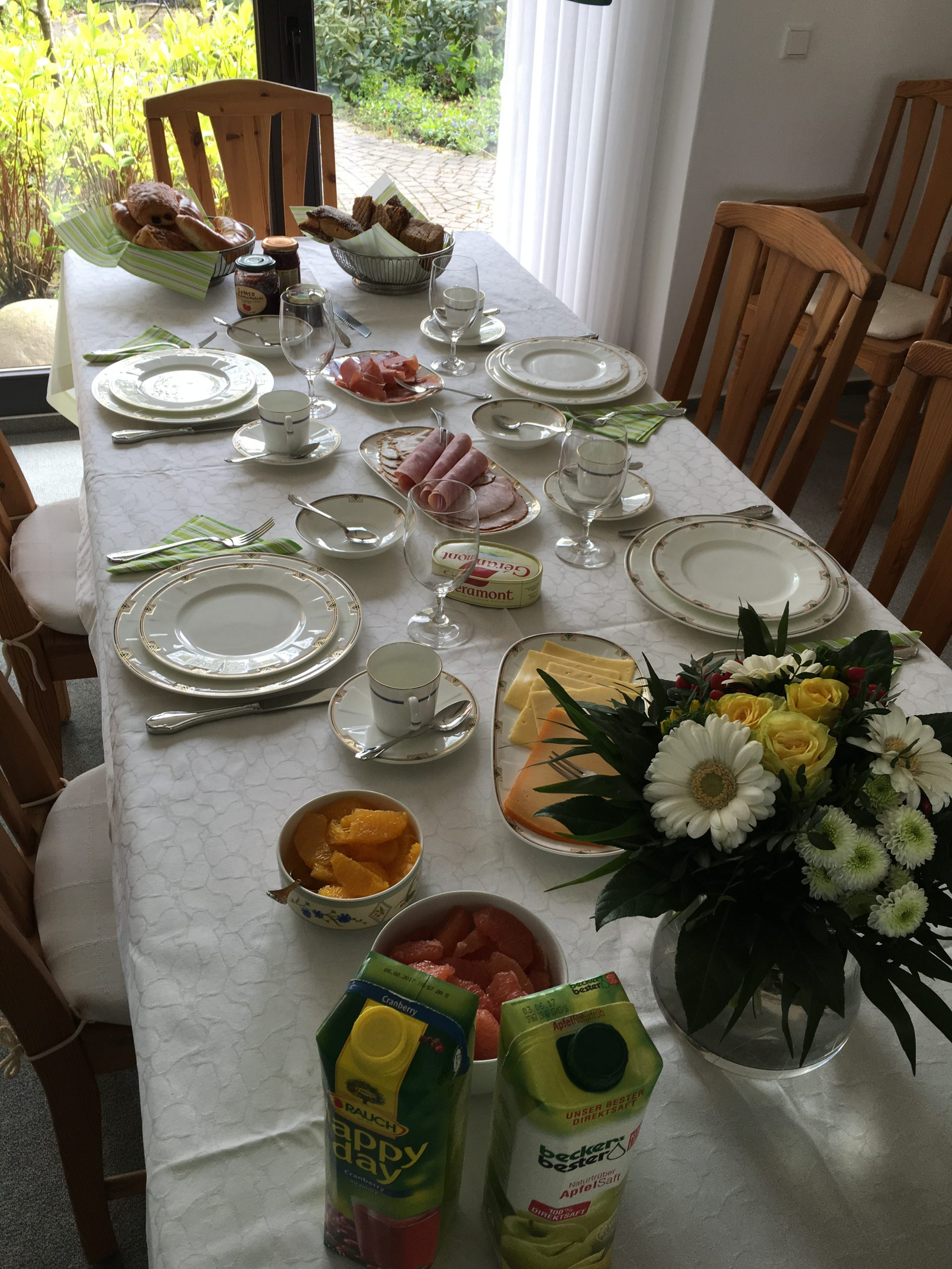a very formal breakfast table with meats, cheeses and breads