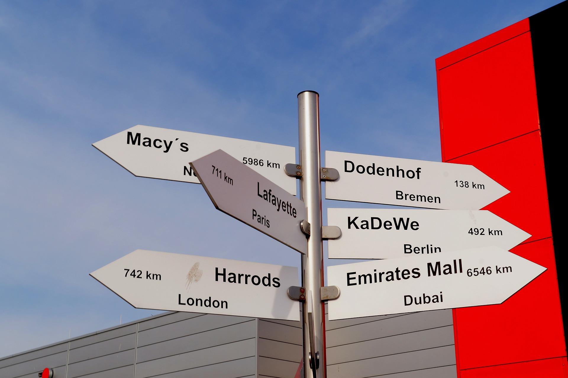 street sign showing Macy's, KaDeWe, Harrods, Emirates Mall