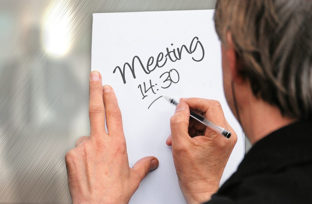 Meeting 14:30 (person making a sign)
