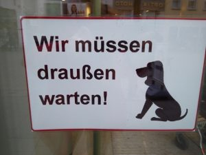 Picture of a sign from a store in Germany: a dog sitting - Wir müssen draußen warten!