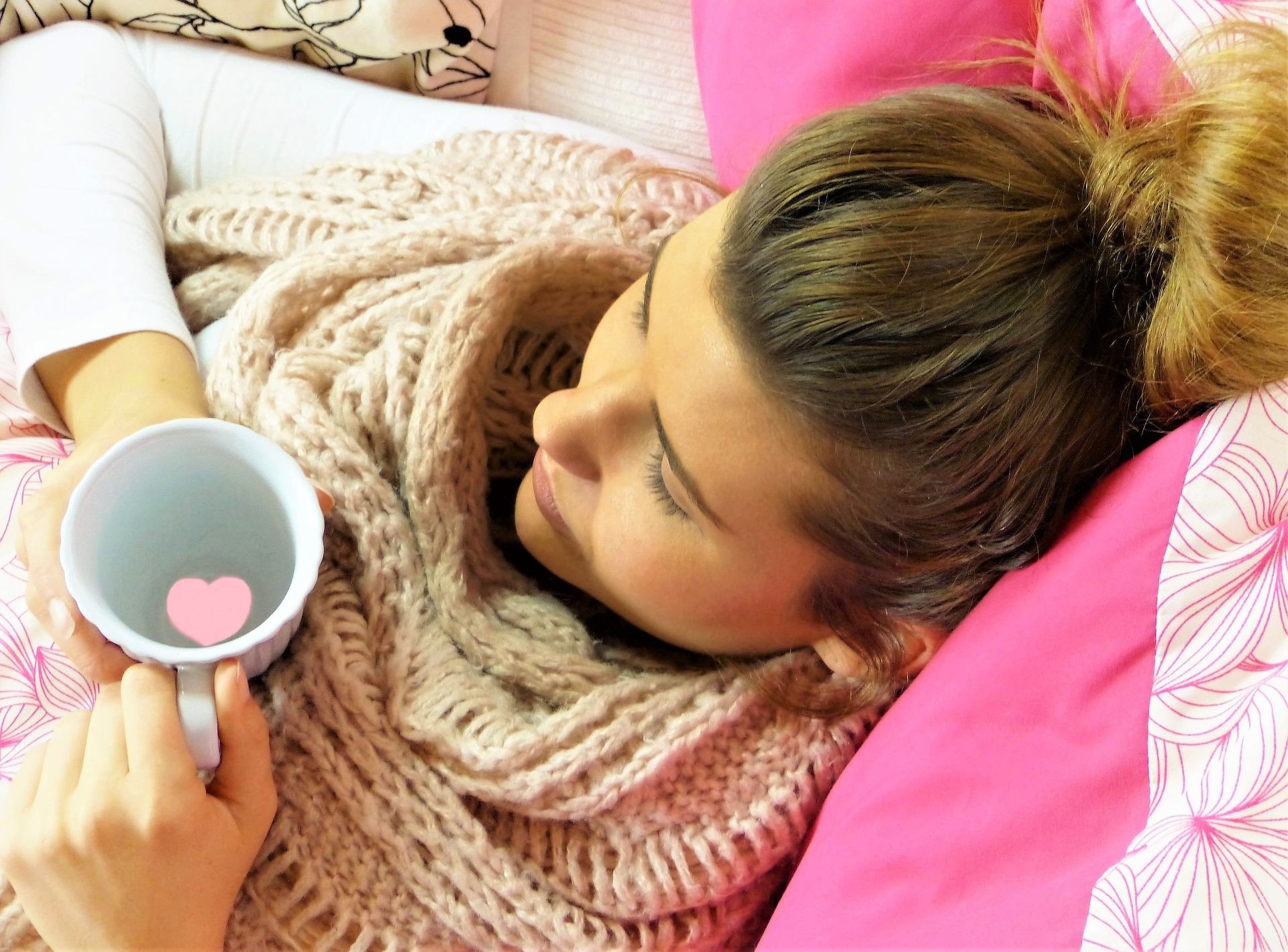 lady laying in bed with a cup of tea